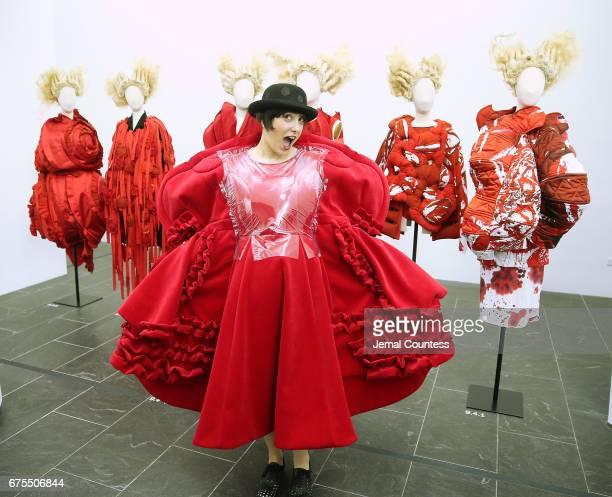 Katherine Zarrella wears fashion by Rei Kawakubo as she poses infront of designs by Rei Kawakubo on display at the 'Rei Kawakubo/Comme des Garcons...