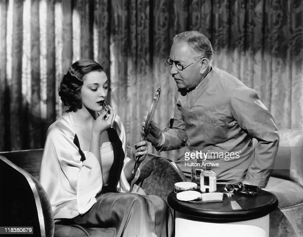 Kathleen Burke US actress applying lipstick while looking in a mirror being held by Max Factor Polish businessman and founder of cosmetics company...
