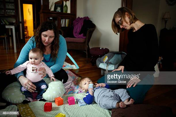Kathleen Gallagher of Lynnfield left holds her five monthold daughter Anna as Morgen Gallo right looks down at her six and a halfmonthold son Rowan...