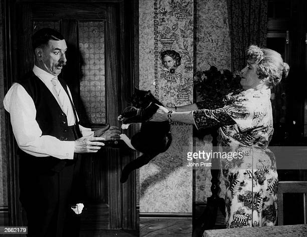 Kathleen Harrison hands 'Lucky' the cat over to costar Cyril Smith in a scene from the play 'Watch It Sailor' at the Aldwych London