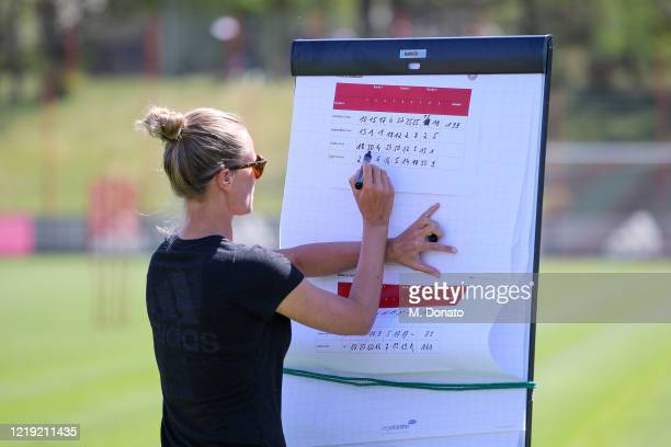 Kathleen Krueger, team manager of FC Bayern Muenchen, writes on the scoreboard during a soccer dart challenge as part of a training session at...