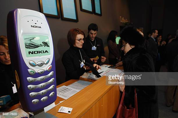 Kathleen Lacy right rents a Nokia cellular telephone at the World Economic Forum from an undentified Nokia worker Tuesday January 24 in Davos...