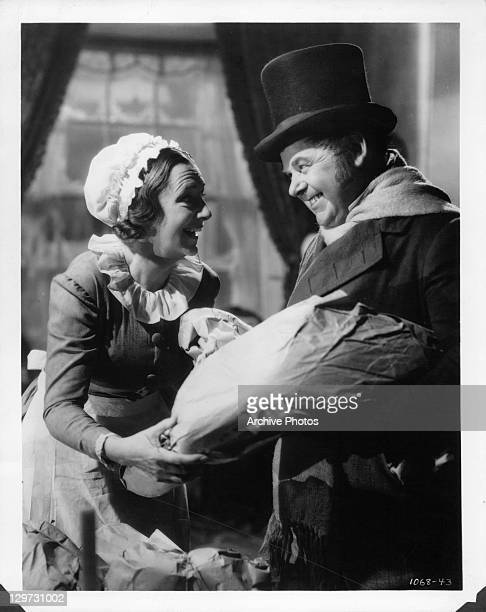 Kathleen Lockhart and Gene Lockhart smiling over wrapped package in a scene from the film 'A Christmas Carol' 1938