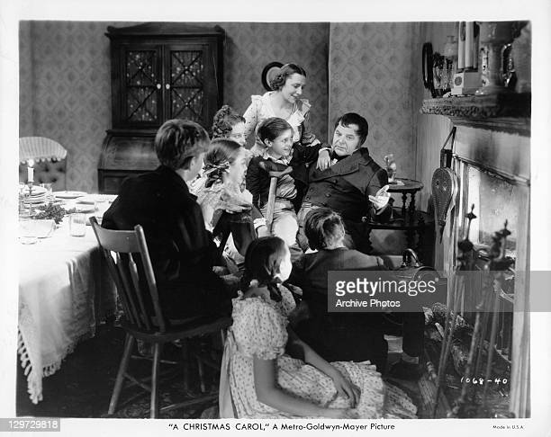 Kathleen Lockhart and Gene Lockhart with children around the fire in a scene from the film 'A Christmas Carol' 1938