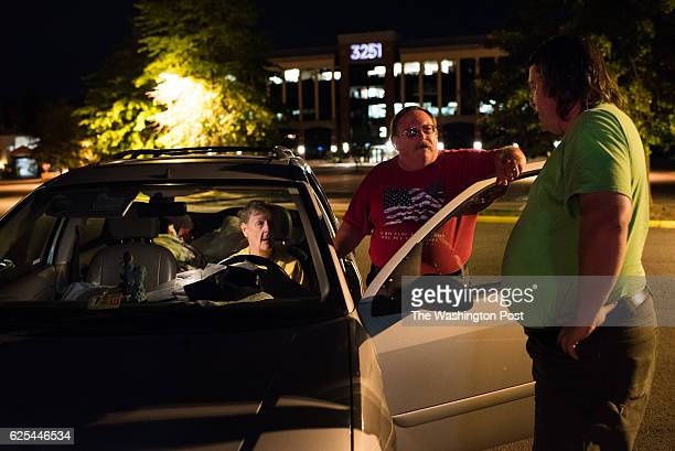 Kathleen McDermott sits in her 2002 Ford Focus station wagon on the night of July 11 as Scott Downey center and John Baird Jr stand nearby She was...