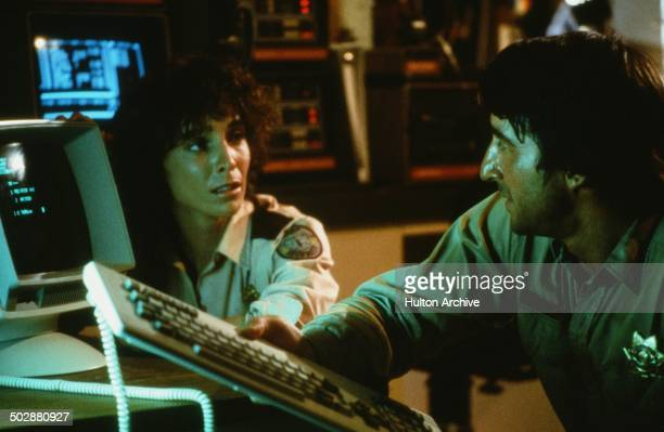 Kathleen Quinlan and Sam Waterston talk at a computer in a scene for the 20th Century Fox movie 'Warning Sign' circa 1985