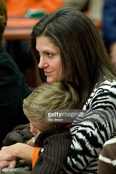 Kathleen Swinney wife of new head coach Dabo Swinney of the Clemson Tigers hold there son Clay during a press conference at Memorial Stadium on...