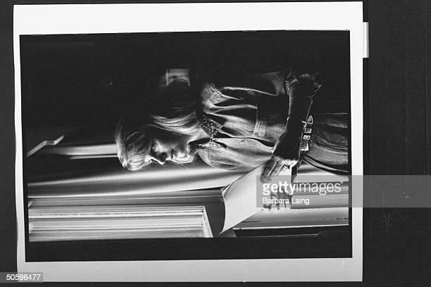 Kathleen Tobin Krueger wife of TX Sen Bob Krueger holding letter written by stalker Thomas Michael Humphrey as she stands by window at home Humphrey...