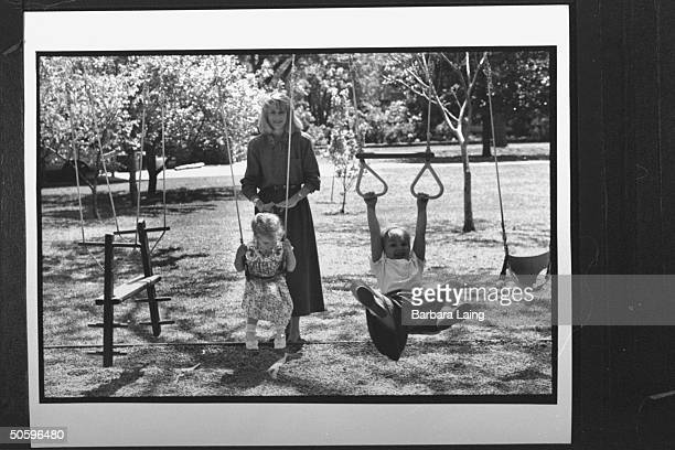 Kathleen Tobin Krueger, wife of TX Sen. Bob Krueger, looking on as her 4-yr-old daughter Mariana & 3-yr-old daughter Sarah romp on backyard swing set...