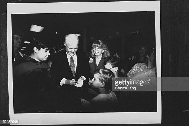 Kathleen Tobin Krueger , wife of TX Sen. Bob Krueger, looking on as OH Sen. John Glenn signs autograph for group of boys at Krueger campaign function...