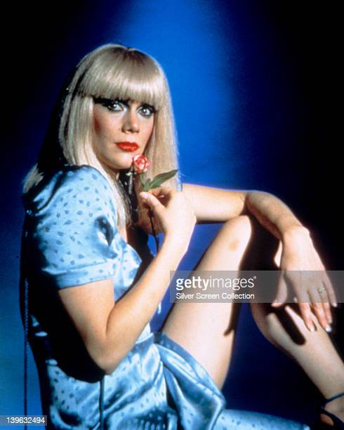 Kathleen Turner US actress wearing a blue silk dress holding a red flower against her face in studio portrait issued as publicity for the film...