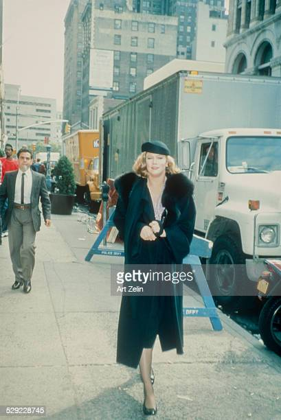Kathleen Turner wearing a black hat and fur trimmed coat walking on the street; circa 1970; New York.