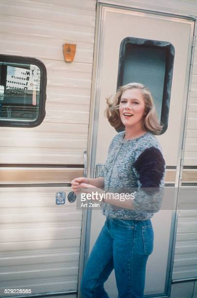 Kathleen Turner wearing a sweater and jeans outside a trailer; circa 1970; New York.