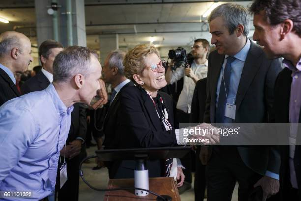 Kathleen Wynne premier of Ontario center shakes hands with an attendee at the MaRS Discovery District in Toronto Ontario Canada on Thursday March 30...