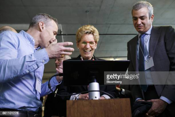 Kathleen Wynne premier of Ontario center watches a demonstration on a tablet device at the MaRS Discovery District in Toronto Ontario Canada on...