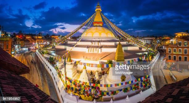 Kathmandu Boudhanath Buddhist stupa prayer flags illuminated dusk panorama Nepal