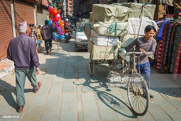 Kathmandu delivery man pushing loaded tricycle through Thamel streets Nepal
