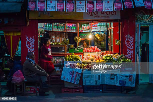 Kathmandu family at fruit stall illuminated at night Patan Nepal