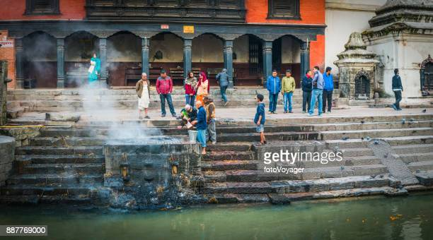 kathmandu mourners at pashupatinath hindu funeral ghats panorama nepal - nepali flag stock pictures, royalty-free photos & images