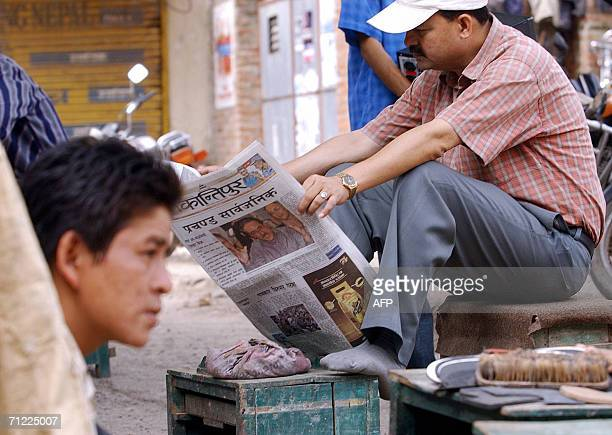Nepalese man goes through a local newspaper carrying a picture of Maoist elusive leader Prachanda on its front-page, in Kathmandu 17 June 2006. A...
