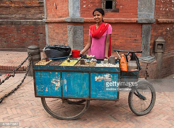 Kathmandu, Nepal - A young, Nepalese woman sells snacks from a cart in Patan Durbar Square.