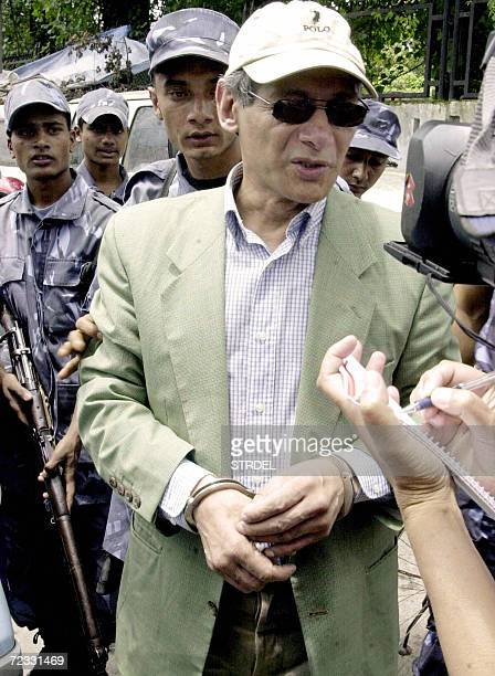 In this photograph taken 14 July 2004, French national Charles Sobhraj talks to media representatives as he arrives escorted by armed police officers...