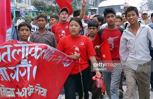 Nepalese Maoist supporters wearing red Tshirts carrying an image of Maoist rebel leader Prachanda and the communist hammer and sickle symbols head...