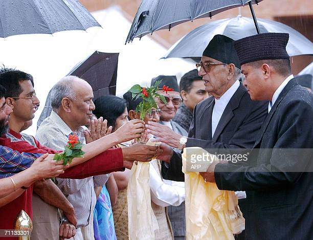 Nepalese Prime Minister Girija Prasad Koirala receives flowers from his party activists at the Tribhuvan International Airport in Kathmandu before...