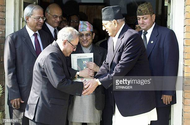 Nepalese Prime Minister Girija Prasad Koirala shakes hands with Indian Foreign Minister Pranab Mukherjee following a meeting in Kathmandu 17 December...
