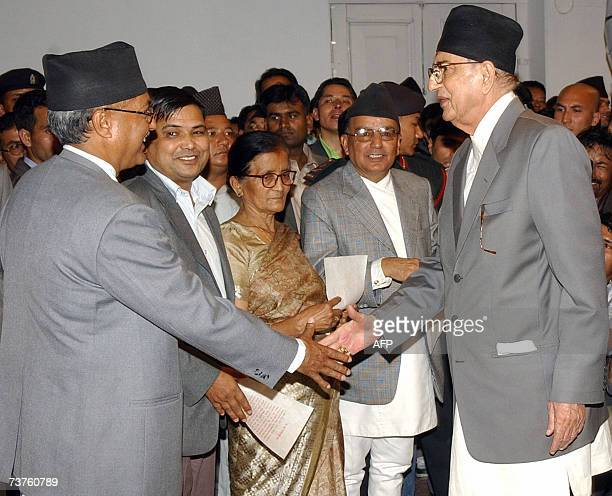 Nepalese Prime Minister Girija Prasad Koirala shakes hands with Education and Sports Minister Pradeep Nepal CPNUML after taking an oath of office for...