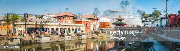 kathmandu pashupatinath hindu funeral ghats mourners on riverbanks panorama nepal - nepali flag stock pictures, royalty-free photos & images