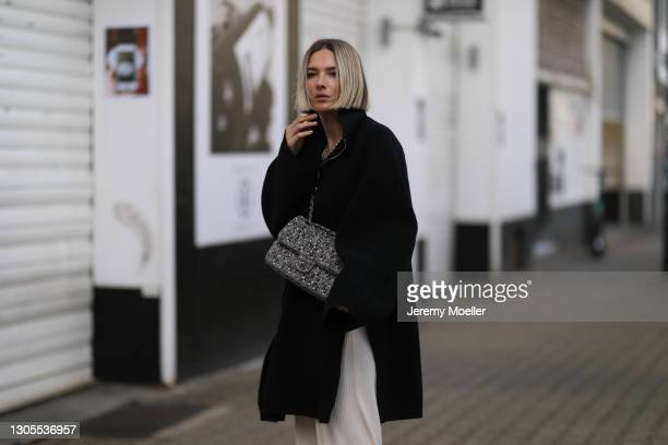 Kathrin Bommann wearing Chanel bag, Toteme black sweater and H&M pants on February 27, 2021 in Dusseldorf, Germany.