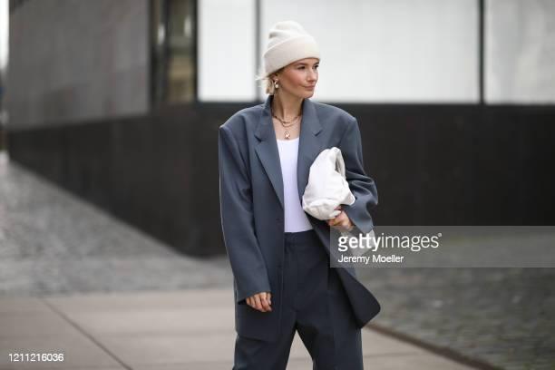 Kathrin Bommann wearing Frankie Shop suit, The Sept top, Bottega Veneta bag, New Balance sneaker and by Aylin König beanie on March 07, 2020 in...