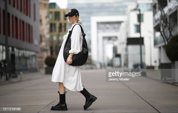 Kathrin Bommann wearing Pixie Shop dress, Bottega Veneta boots, Frankie Shop bag and, New Era cap on March 07, 2020 in Cologne, Germany.