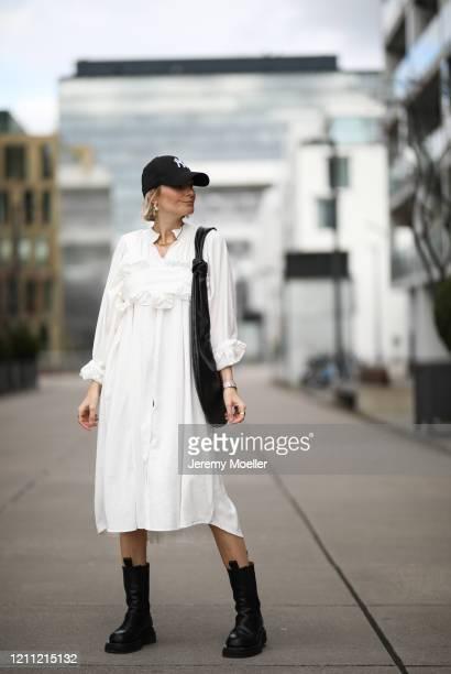 Kathrin Bommann wearing Pixie Shop dress, Bottega Veneta boots, Frankie Shop bag and, New Era cap on March 07, 2020 in Cologne, Germany.