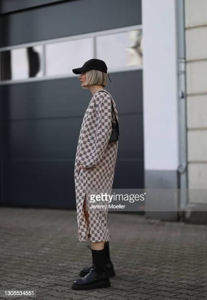 Kathrin Bommann wearing Prada black cap, Old Celine black leather bag, Baum & Pferdgarten midi dress and Bottega Veneta black boots on February 27,...