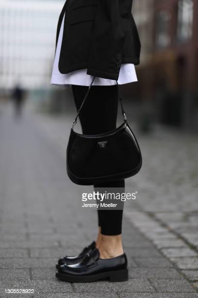Kathrin Bommann wearing Prada jacket and loafer, Vival white shirt, Calzedonia black leggings and Prada Cleo bag on February 27, 2021 in Dusseldorf,...
