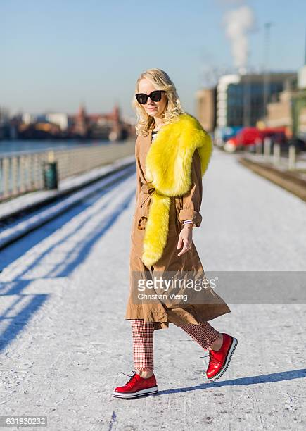 Kathrin Gelinsky wearing a brown Marc Cain trench coat yellow fur scarf sunglasses striped top Marc Cain salmon colored checked pants red shoes Marc...