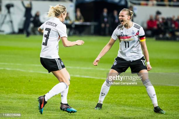 Kathrin Hendrich of Germany celebrates scoring the 10 goal with teammate Alexandra Popp during a womens international friendly between Sweden and...