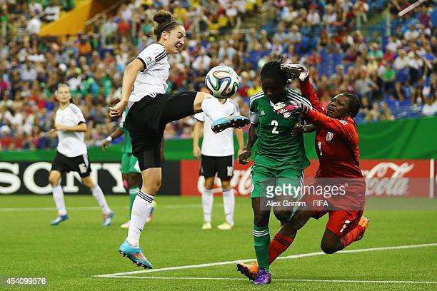 Kathrin Schermuly of Germany is challenged by Ebere Okoye and goalkeeper Sandra Chiichii of Nigeria during the FIFA U20 Women's World Cup Canada 2014...
