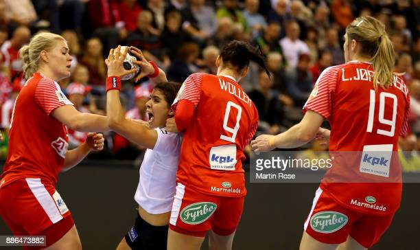 Kathrine Heindahl and Fie Woller of Denmark challenge Rakia Rezgui of Tunisia during the IHF Women's Handball World Championship group C match...