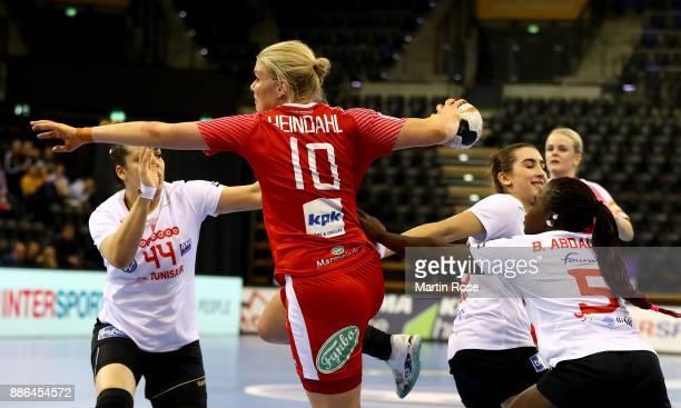 Kathrine Heindahl of Denmark challenges Manel Kouki of Tunisia during the IHF Women's Handball World Championship group C match between Denmark and...
