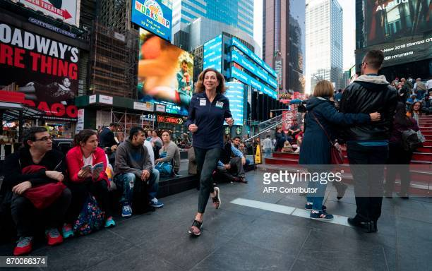 Kathrine Switzer who was the first woman to run the Boston marathon runs through Times Square November 2 2017 in New York Switzer plans to run in...