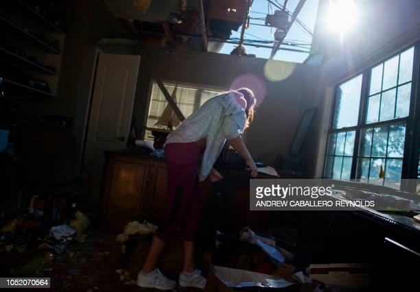 Kathryn Arnold picks up clothes from the floor of her family house in Port St Joe beach Florida on October 13 three days after hurricane Michael hit...