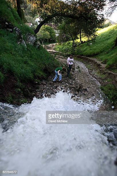 Kathryn Jewell and her nineyearolddaughter Grace investigate a waterfall that the rain has created near their home in Chevy Chase Canyon as southern...