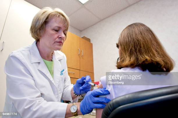 Kathryn Quinn a nurse practitioner left administers a flu shot a MinuteClinic facility inside a CVS store in Wyckoff New Jersey US on Tuesday Sept 1...