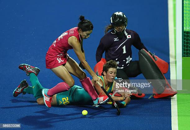 Kathryn Slattery of Australia is stopped by Japan goal keeper Sakiyo Asano and Emi Nishikori during the Women's group A hockey match between...