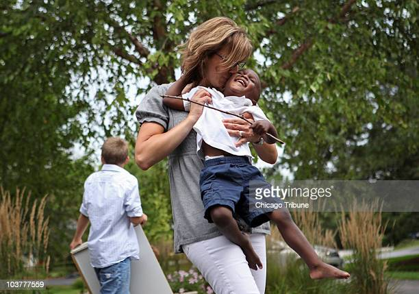 Kathy Hart center kisses her son Allen while she plays with her children outside her home in Long Grove Illinois August 17 2010 Hart a cohost of the...