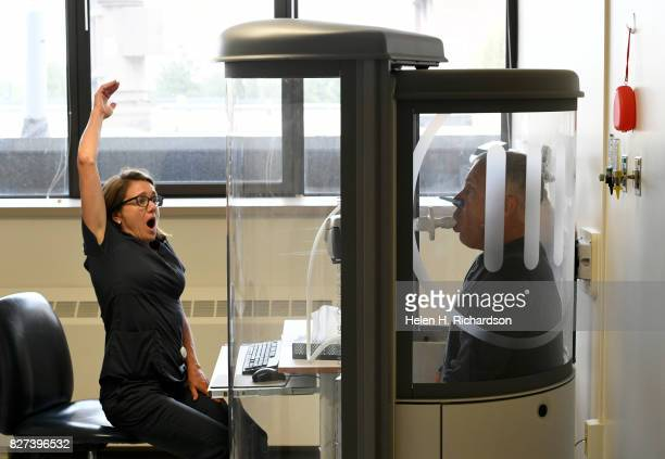 Kathy Kramer a respiratory therapist left asks her patient John Castona right to take big deep breathes during a routine pulmonary function test at...