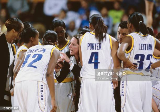 Kathy Olivier, Head Coach for the University of California, Los Angeles UCLA Bruins gets in the huddle to pass instructions on to the team during the...
